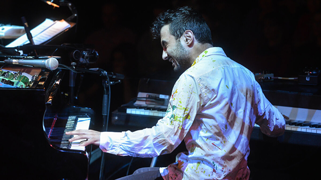 Tigran Hamasyan sitting down and playing two pianos, one with each hand.