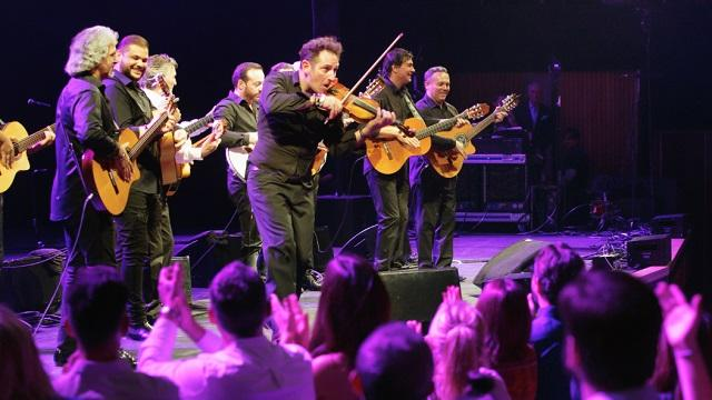 The Gipsy Kings' band members play their violins and guitars on stage in front of a crowd.