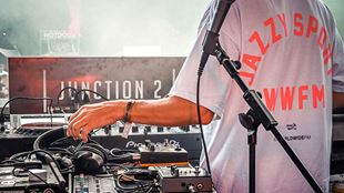 "A view from behind of a DJ on the decks, with the words ""Junction 2"" set against a hazy background."