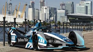 A blue and white Formula E racing car is parked on the docks in London with the O2 and the Emirates Air Line cable cars as a background.