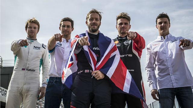 Five British drivers of formula E standing next to each other, their fingers pointing at the camera.