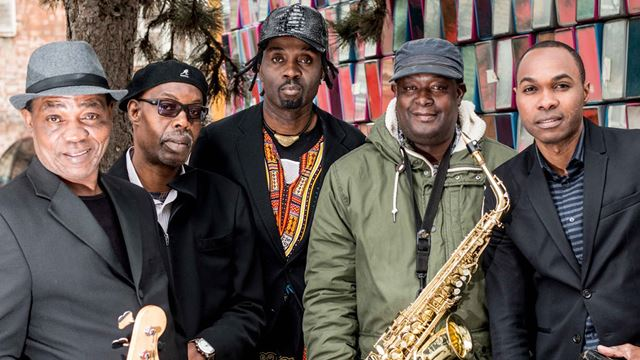 The five members of Kasai Masai smile for the camera, one member holds a saxaphone.