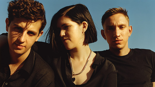 Romy Madley Croft, Oliver Sim and Jamie Smith from The XX in front of a blue background.