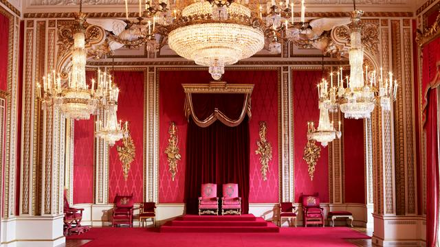 The Throne Room at Buckingham Palace, featuring two red throne chairs, red carpet and chandeliers.