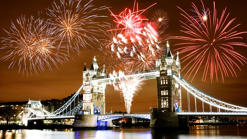 Fireworks explode in oranges and reds over Tower Bridge on Bonfire Night.