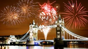 Fireworks explode in oranges and reds over Tower Bridge.