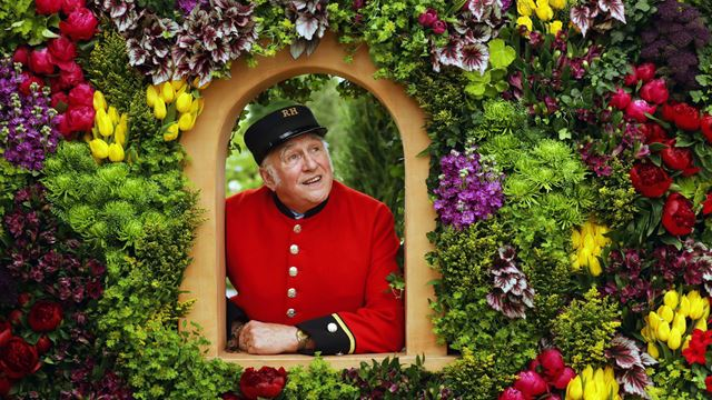 A Chelsea Pensioner poses on the Marks and Spencer Spirit of Summer: A Mediterranean Journey exhibit at the RHS Chelsea Flower 2017.