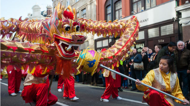 During Chinese New Year parade in London, a group of people is celebrating and walking in the streets with a giant paper mache red and gold dragon.