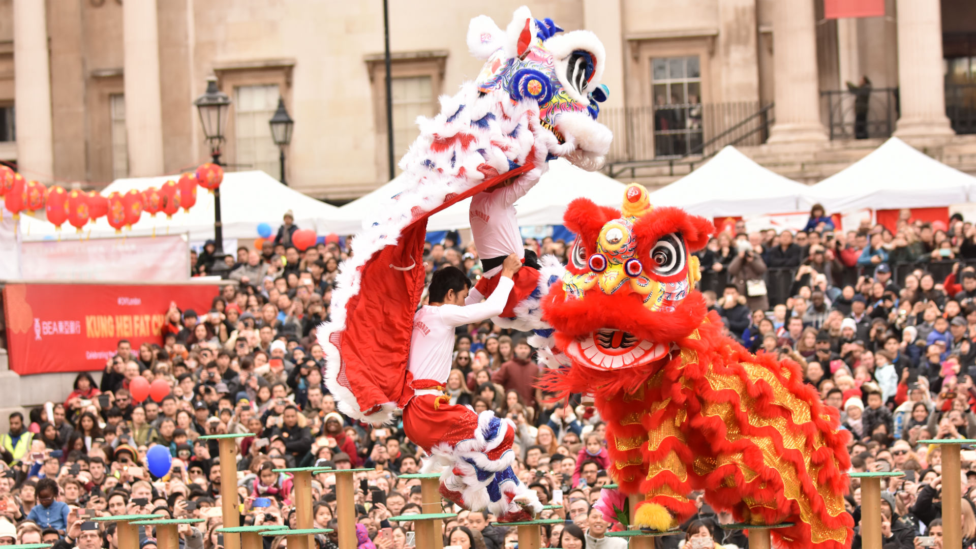 Two people jump from pole to pole during traditional lion dances in Trafalgar Square.