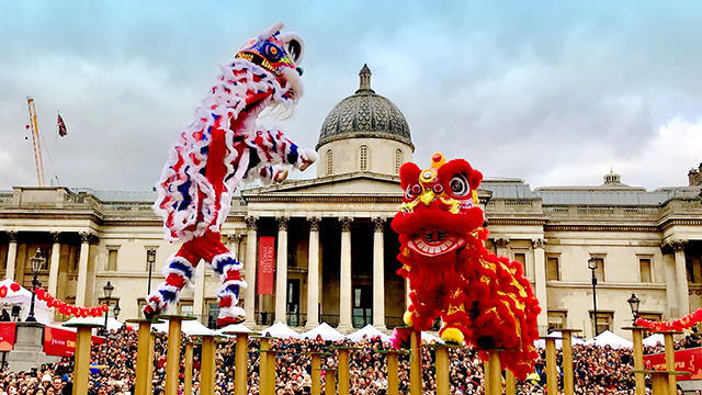 Two lion dance teams balance on yellow poles in Trafalgar Square, with crowds of people and the National Gallery behind.