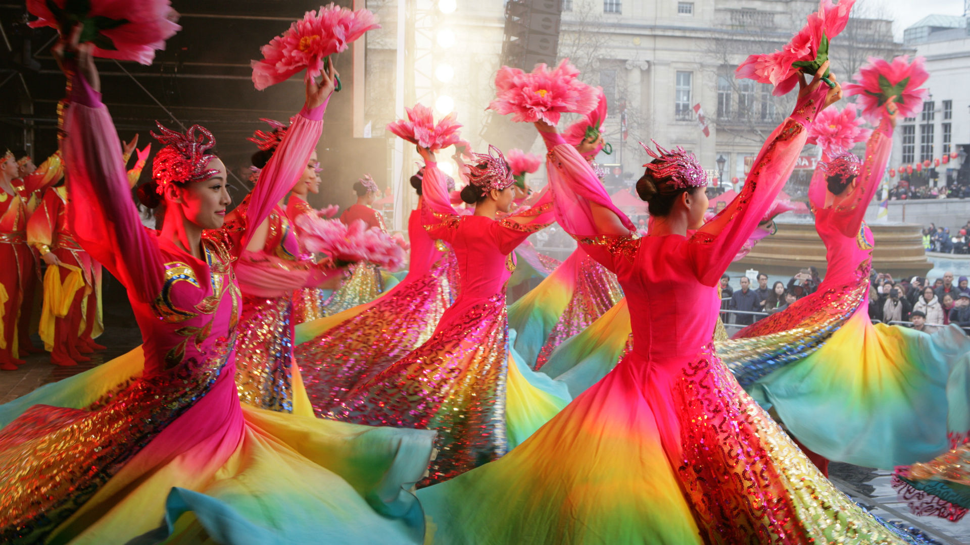 A group of brightly dressed dancers perform on a stage in front of crowds in Trafalgar Square during Chinese New Year in London