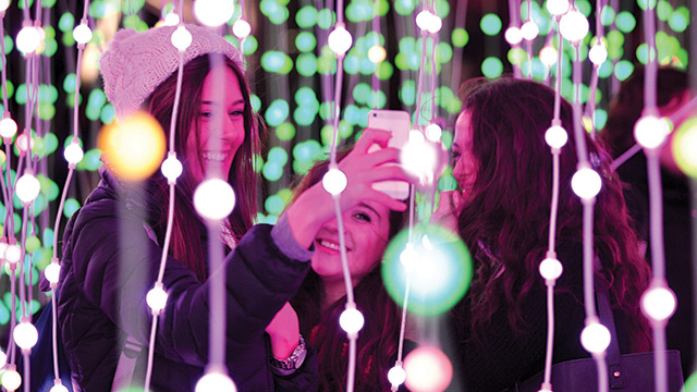 Three women take a selfie among strings of green and white fairy lights at night.