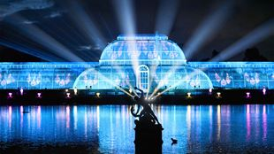 The Palm House across the lake is illuminated with blue lights, as blue laser beams shine into the dark sky.