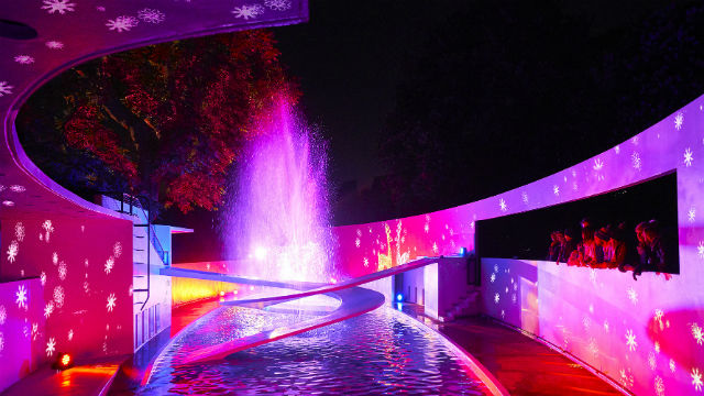 People watching the fountains at the Lubetkin penguin pool. The pool is bathed in pink light and the walls have snowflakes projected on to them.