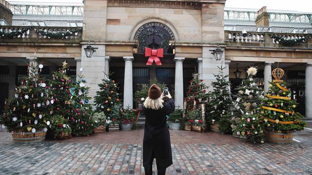 A lady taking a picture of Covent Garden's Christmas trees set against the Covent Garden Piazza.