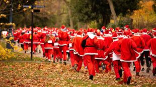 Hundreds of people in Santa costumes take part in the Santa Run in Victoria Park.