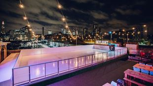 The ice skating rink at Skylight rooftop in the evening, with fairy lights above the rink and views across London.