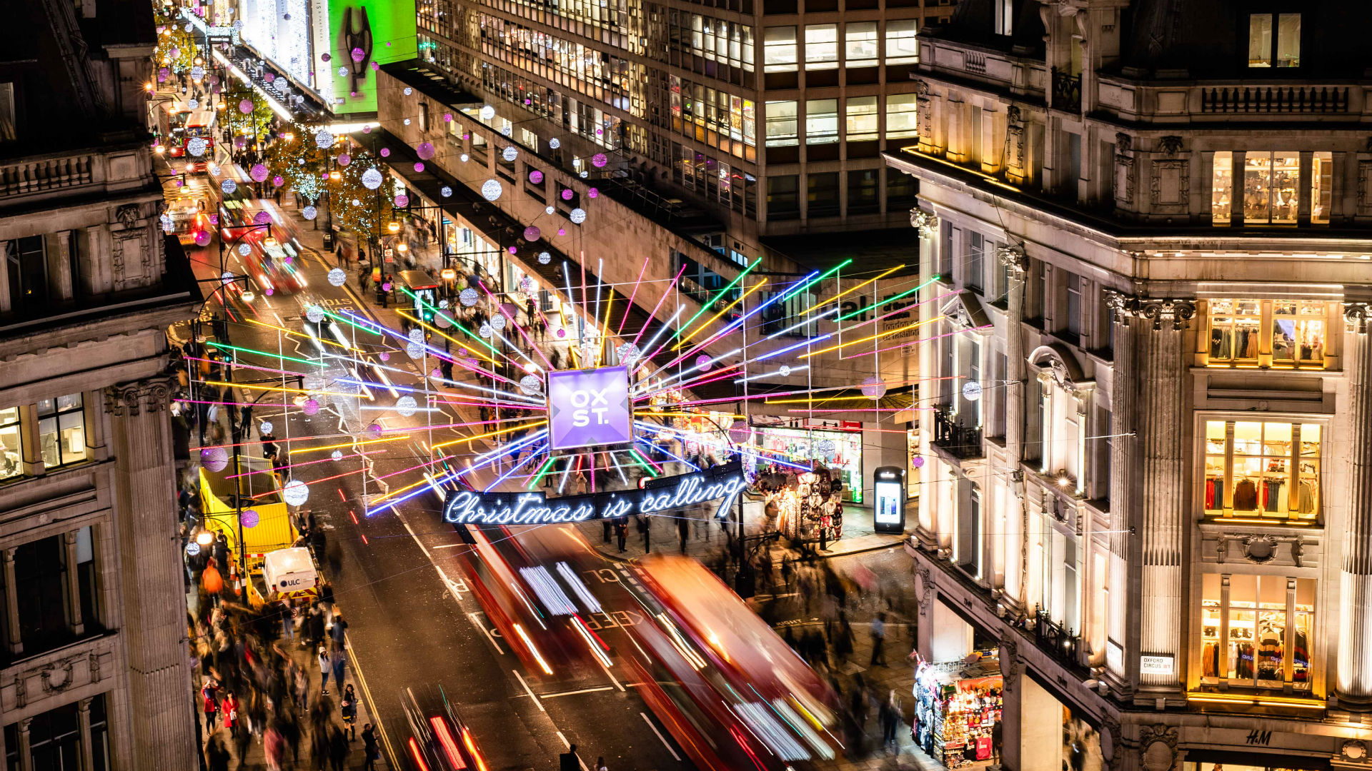 Rainbow-coloured Christmas lights sparkle above the buzzing streets of Oxford Street at night.