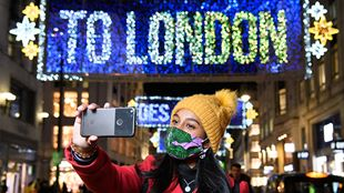 "A lady wearing a face covering and a yellow bobble hat takes a selfie of the blue and yellow Oxford Street lights, which read ""TO LONDON""."