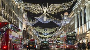 White angel-shaped Christmas lights span the two sides of Regent Street at night, with buses and taxis on both sides of the road.