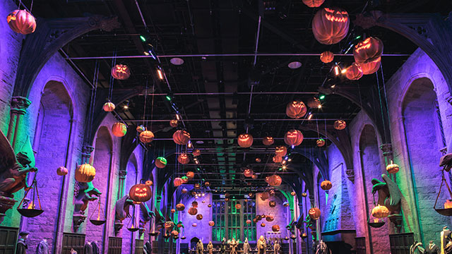 Floating orange pumpkins hanging from the ceiling of the Great Hall, lit up in green and purple light