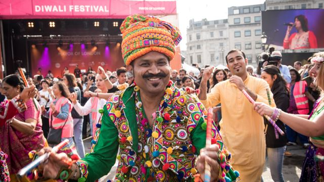 A man dressed in traditional clothing with flower garlands around his neck, at the Diwali festival, while other performers dance in the background.
