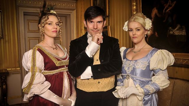 Three actors, dressed in period costume, look at the camera.