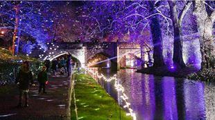 People walking along the river and light illuminations at Enchanted Eltham Palace