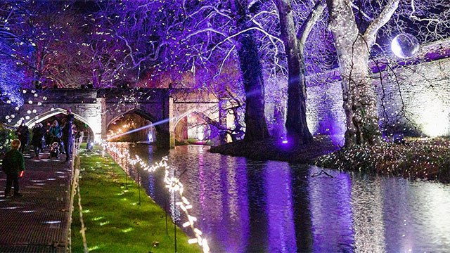 Purple and white illuminations light up the water and bridge over the ancient moat at Eltham Palace.