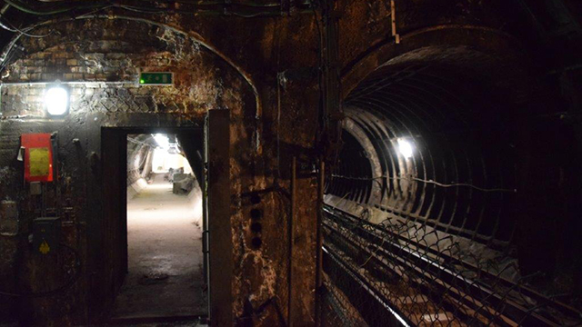 A dimly lit, disused Tube tunnel, track and platform that's lit only by two lights.