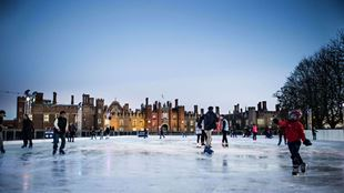 A few skaters skate around a fairly empty ice rink at dusk, with Hampton Court Palace in the background.