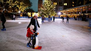 A lady, dressed in a black coat and white hat, stands next to a child wearing a white hat and red coat on an ice rink at night. The child is holding onto a penguin-shaped stabiliser and an illuminated Christmas tree and the Natural History Museum are in the background.
