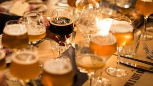 A candlelit table filled with glasses of beer