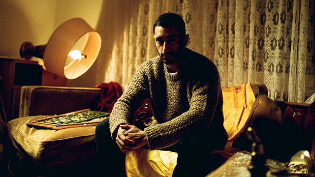 A man sits on a chair in a dimly lit room, with a light and drawn curtains behind.
