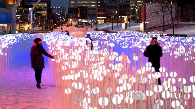 Two women walking through a luminous installation