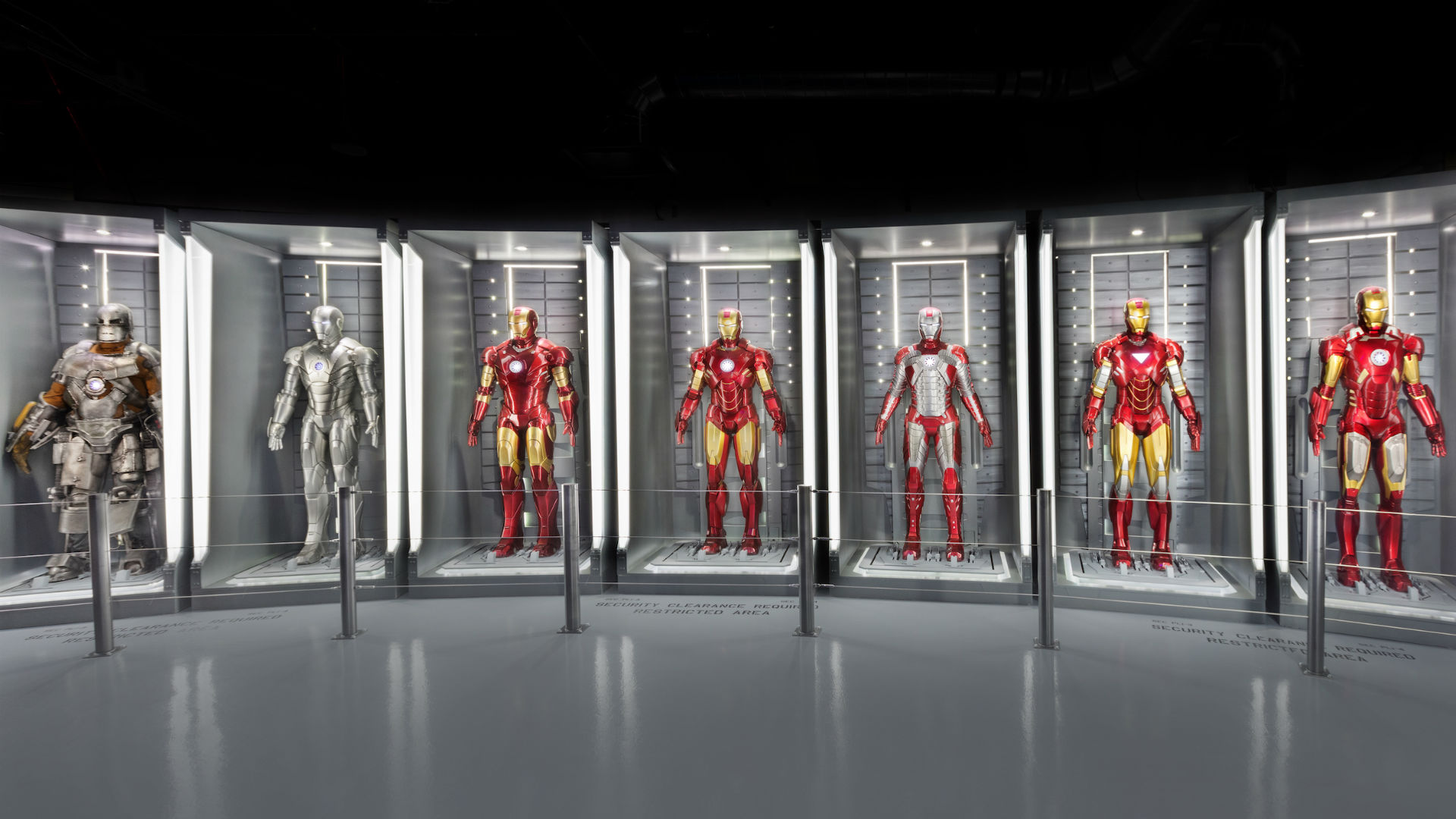 Seven tall display cabinets with seven different superhero outfits displayed within
