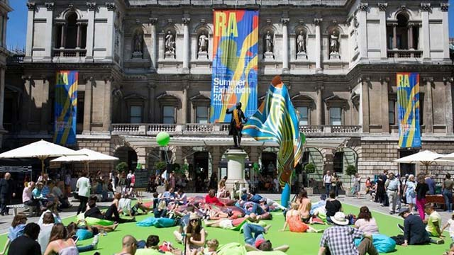 People sit on bean bags and grass on a sunny day in the courtyard at the Royal Academy.