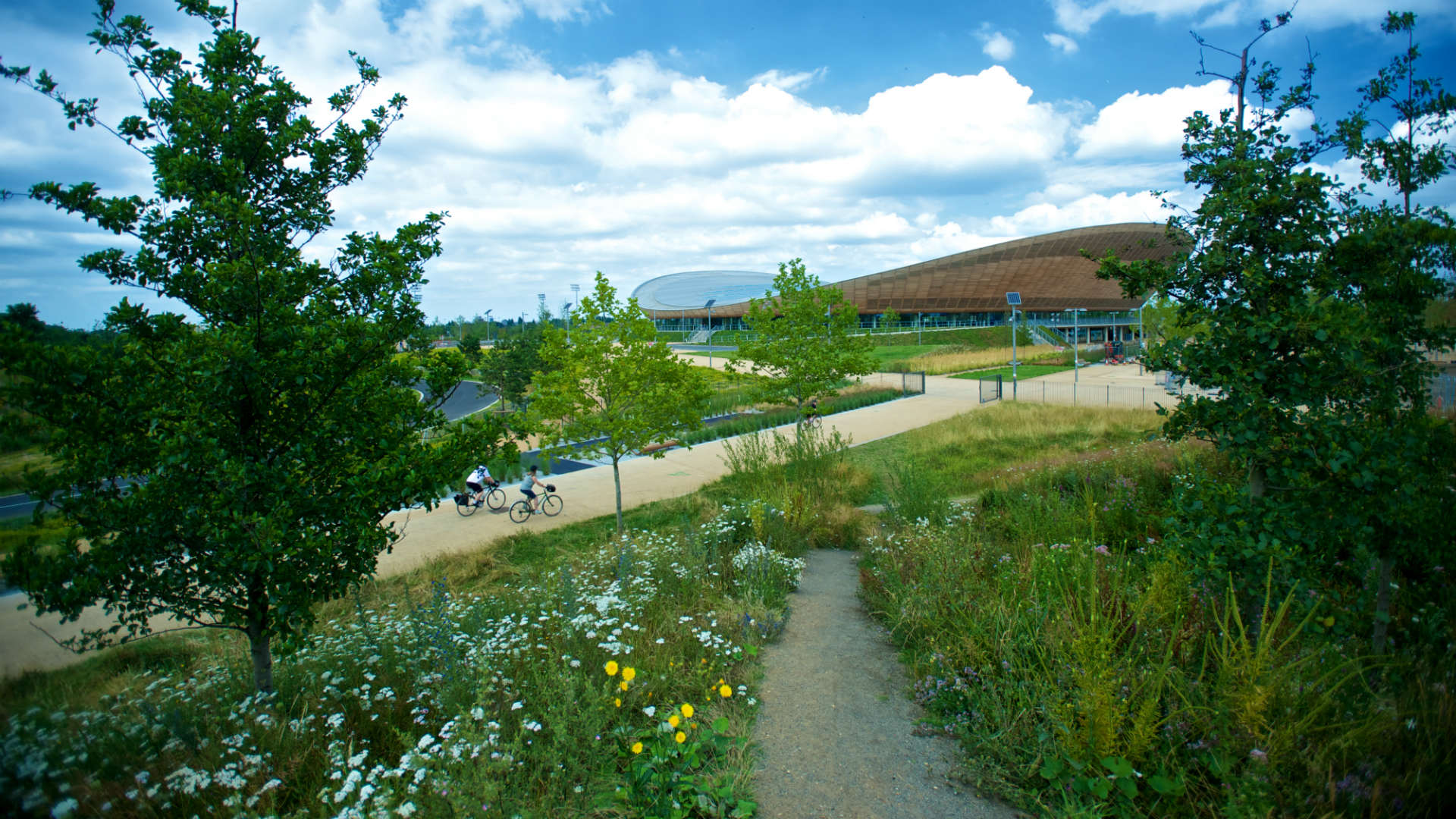 Green grass of Queen Elizabeth Olympic Park with the Velodrome in the background