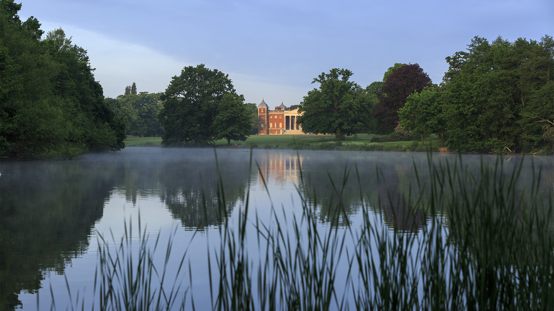A view through the reeds across a lake to Osterley Park and House in the distance.