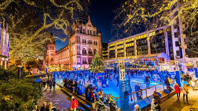 Ice skaters enjoying themselves at the Natural History Museum's open-air ice rink after dark.