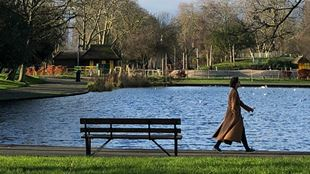 A person wearing a winter coat, walking by a bench in a park.