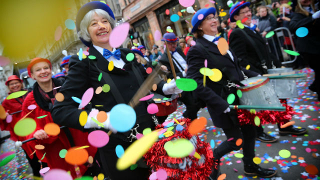 A drumming band parading through a flurry of confetti