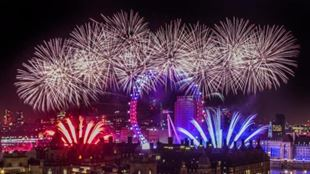 Red, white and blue fireworks explode around the Coca-Cola London Eye on New Year's Eve.