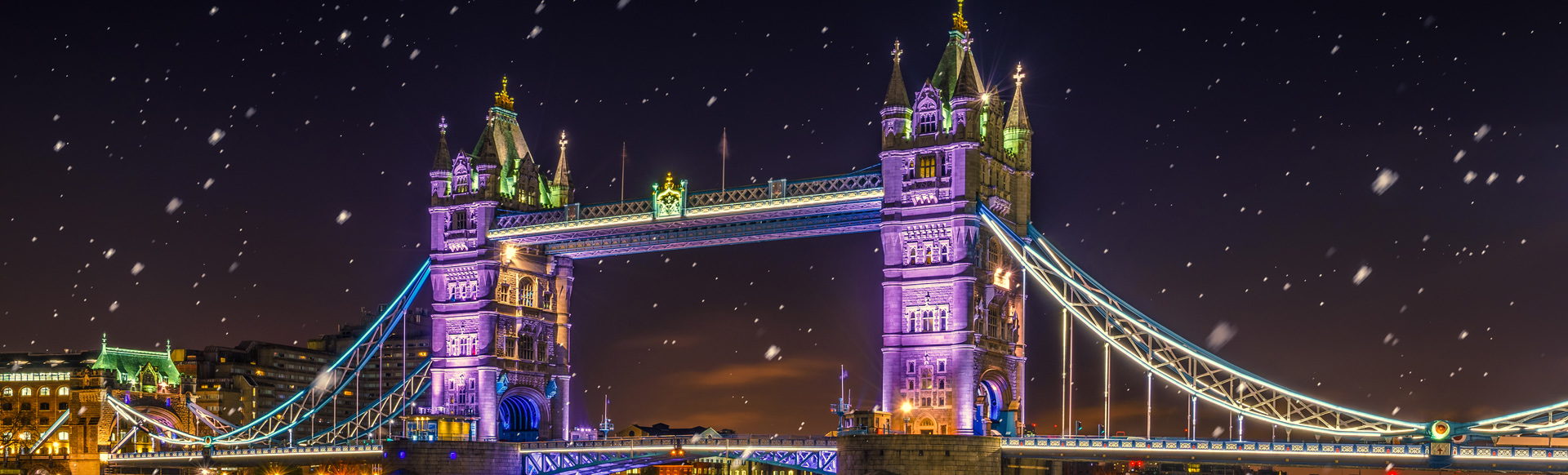 Tower Bridge lit up at night in purples and yellows.