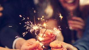 People holding sparklers and smiling.