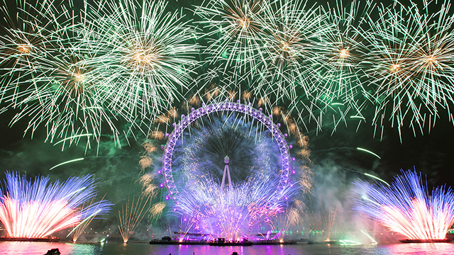 Green and purple New Year's Eve fireworks surround the London Eye.