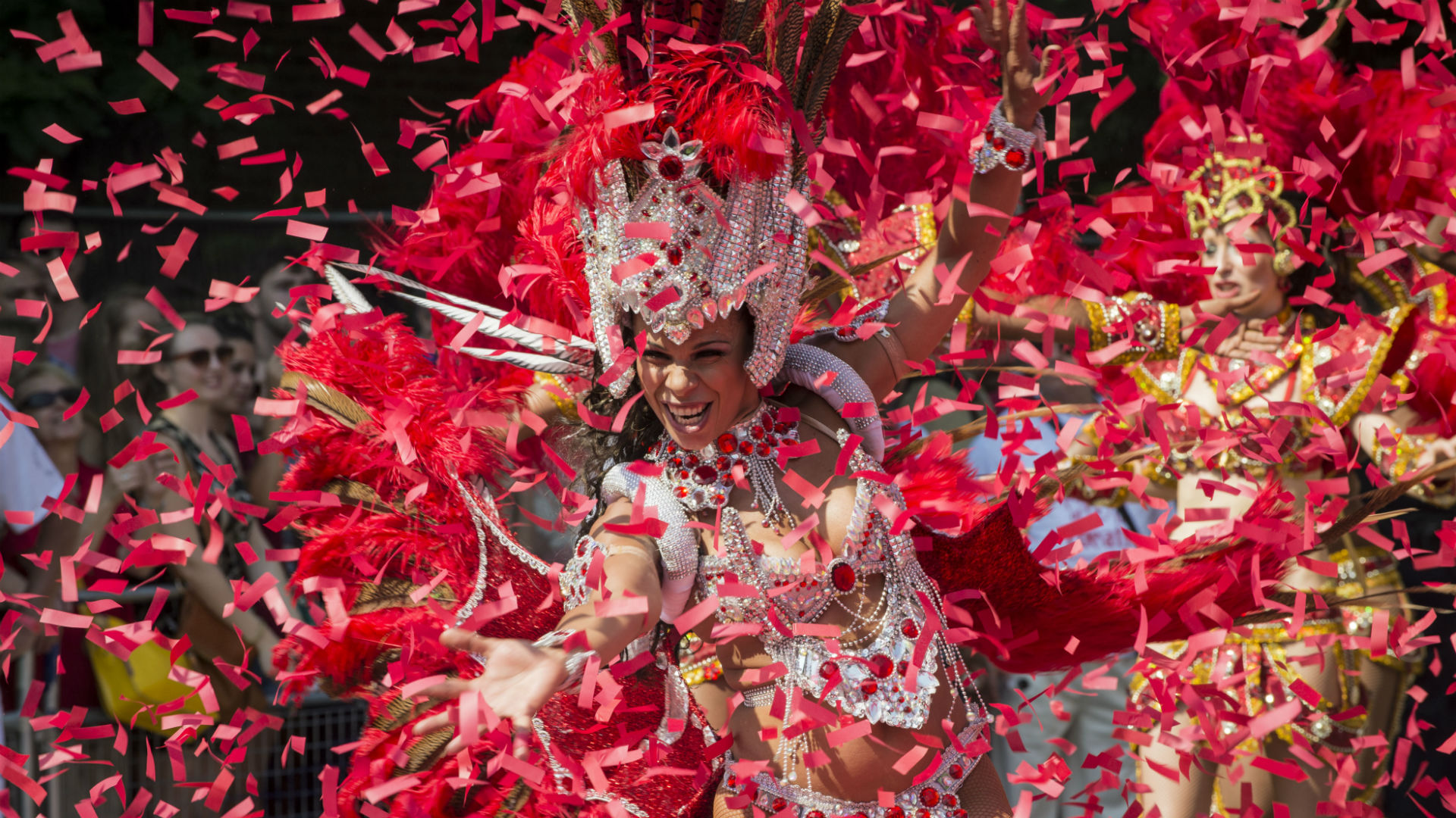 A Notting Hill Carnival performer dances while surrounded by confetti