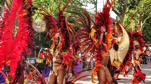 A photo of performers enjoying the Notting Hill Carnival 2016, dressed in red costumes.