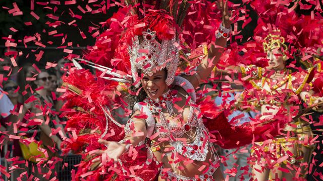 A Notting Hill Carnival performer dances surrounded by red confetti.