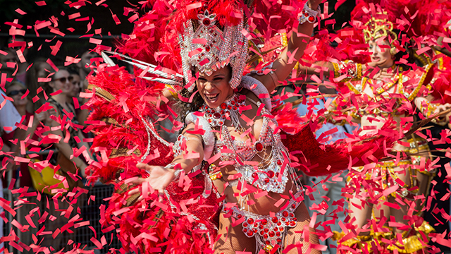 A lady, dressed in a carnival headdress and clothing, dances as red ticker tape fills the air.